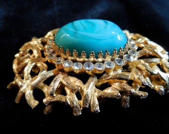 Castlecliff stunning brooch with huge center stone of faux turquoise, circled by clear rhinestones nesting on a bed of twisted gold branches