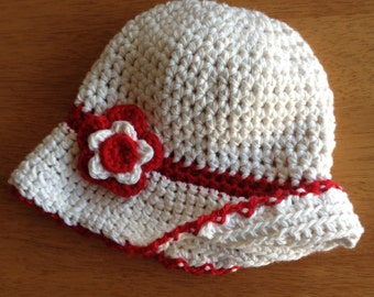 Girls crochet sunhat with small peak and flower detail. Off-white cap with red and off-white flower. Other colours available.
