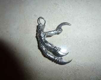 A silver crows foot pendant.