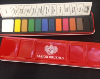 Water colour paint tin containing 12 blocks of colour