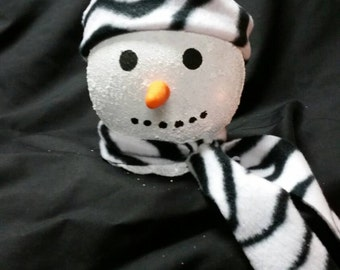 Cute light up snow person with black and white zebra print hat and scarf
