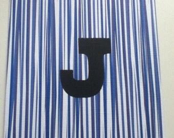 """Letterpress overprinted """"J"""" in deep black ink."""