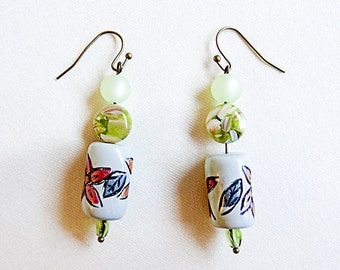BEADED DANGLE EARRINGS with brass ear wire. Center bead is pale green glass with painted floral design. Three green beads - 0491+