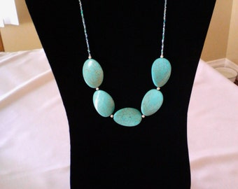 Turquoise colored curved beads with silver and seed bead statement necklace.