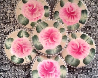 Handpainted coasters trimmed in faux pearl beading. This set includes 6 coasters.
