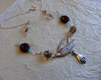 A bird in hand - mixed media, czech glass and tiny quartz crystal beads, sterling silver and silver ox plated silver.