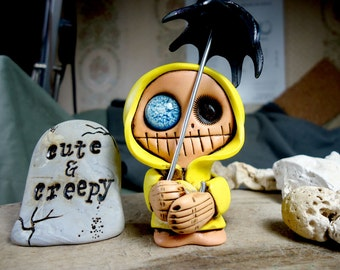 Suso, a little monster in the rain. Cute skeleton with umbrella dressed in yellow oilskin.