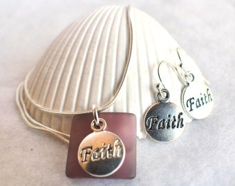 Sea glass necklace in burgundy with round silver faith charm on chain with matching earrings.