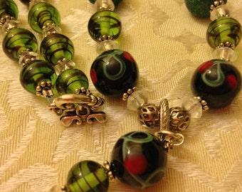 Handcrafted black and green necklace, strung with vintage beads. Comes with matching earrings.