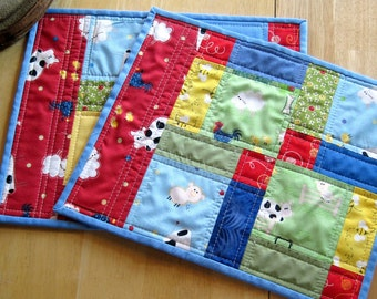 Set of two quilted place mats with farm animals for children in primary colors. 13 inches by 10.5 inches each.