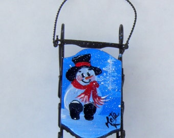 Hand Painted Sled Ornament with a Snowman in the Woods on it