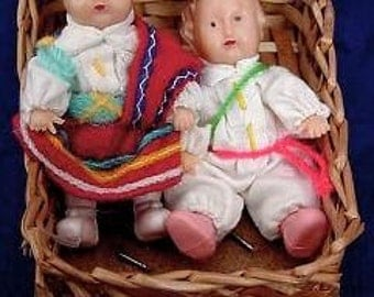 A Pair of Hard Plastic Ethnic Baby Dolls in Wicker Sled