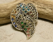 Vintage leaf style dress clip with multi colored rhinestones circa the 1940s.