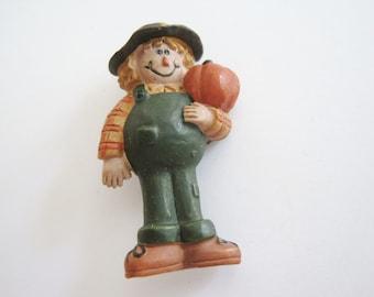 Vintage Plastic Autumn Scarecrow Pin Holding an Orange Pumpkin