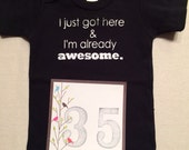 DISCOUNTED -- Nearly Perfect -- #35b, see photos -- I just got here & I'm already awesome.  -- black snapsuit, size 0-3 months