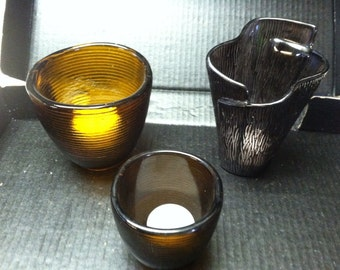 Three glass candle holders. Or can be serving dishes.