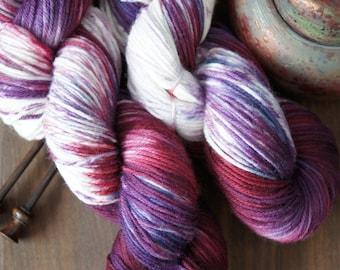 "Hand Dyed Yarn Superwash Merino . DK . 243 yards . ""Blaubeere"" . Shades of Pink and Purple on a white canvas"