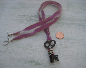 Vintage Key neckace placed on purple ribbon
