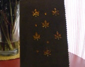 Book cover with self book marker out of brown sueded fabric with acrylic leaves on the cover.