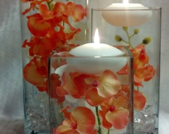 three square vases with coral orchids and floating candles/coral orchid centerpiece/coral orchid wedding/lit floating candle square vases