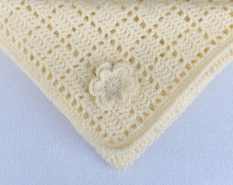 Crochet baby blanket in cream.