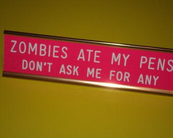 "Zombies Ate My Pens...  engraved 2"" x 8"" pink sign/white letters - 2 lines with gold desk holder"