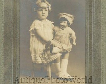 Beautiful girl on chair posing with large doll antique toy photo