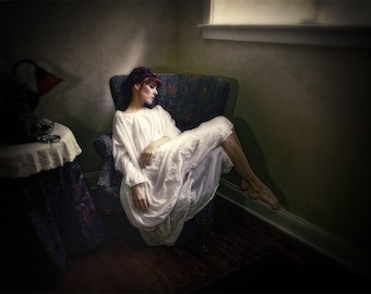 Leeds--  Woman dressed in a long white gown sleeping in a chair as morning light streams through the window.