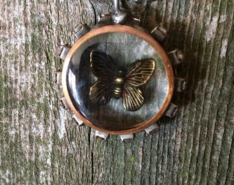 Soldered Copper bezel with a butterfly and filled with Resin