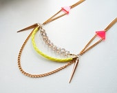 Andrion – Necklace, neon yellow cord, neon pink triangles, gold-plated chain, bronze-colored spikes, glass beads, gold-filled clasp