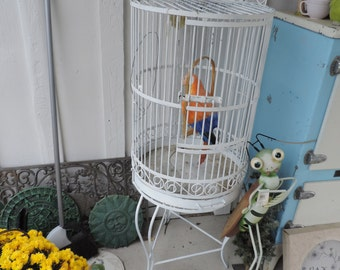 Vintage wrought iron birdcage on stand.