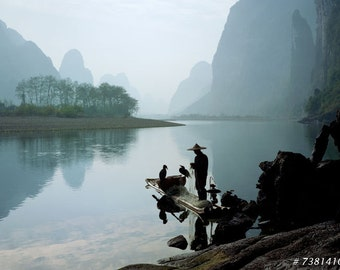 Fisherman with cormorant birds on Li River, Guilin, China. Asia travel landscape photography.