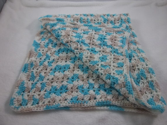 Crocheted baby afghan in blue white and tan variegated yarn.