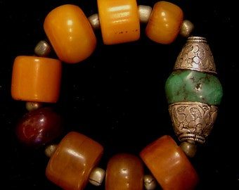 Egyptian copal bracelet with Tibetan silver capped turquoise focal bead. Strung on rubber gasket, stretches to fit.