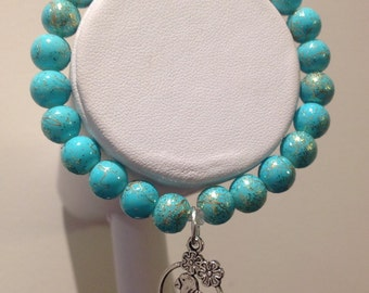 Bracelet. 18cm Features 8mm aqua glass beads. Glittery effect to beads. Beige patternst