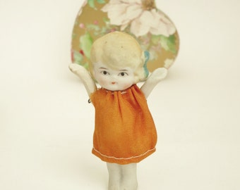 Antique Doll with Mobile Arms made in Japan - Bisque Porcelain - Blonde doll with blue bow and orange dress