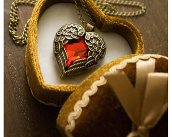 my devils heart is ruby red - dapper necklace featuring faceted crystal heart held captive by studded brass wings and chain