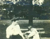 Little Boy Playing With His Hat on Park Bench Mother Holding Umbrella Watching Him Vintage Antique Black and White Photo Photograph