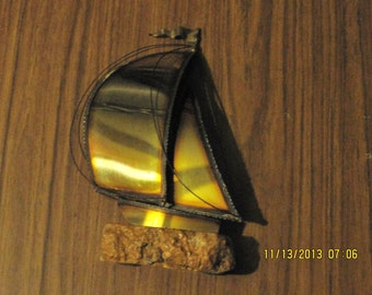 vintage copper sail boat on rock