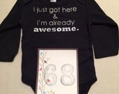 DISCOUNTED -- Nearly Perfect -- #68b, see photos -- I just got here & I'm already awesome.  -- black snapsuit, size 3-6 months