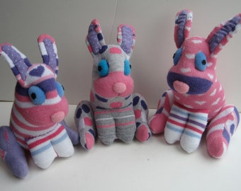 "CHARLIE""S ANGELS are 3 sister sock bunnies in pretty pinks and purples. They are child safe and cute as can be."