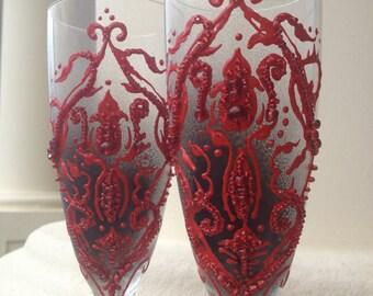 Wedding champagne glasses, toasting flutes with a dark red damask on a black background, wedding reception, bridal shower, Halloween wedding