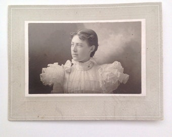 Vintage/Antique cabinet  photo of a woman in a dress with a curly bangs