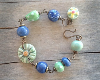 Whimsical Colorful Green and Blue Ceramic Flowers and Blue Ceramic Bead Brass bracelet