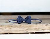 Navy blue butterfly headband on skinny elastic