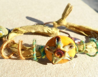 Shooting Star- handmade lampwork bead wooly wire and recycled sari silk mixed-media bracelet  in yellow ocher rainbow raku and teal