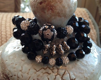 Faceted black onyx bracelet set with pace crystal balls and pewter pieces.