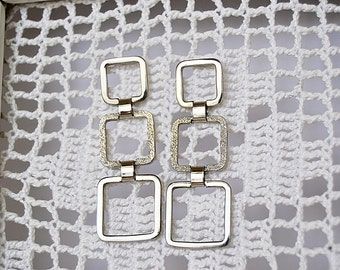 long silver earrings with three square