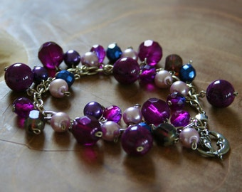 Magic: a charmbracelet with a lot of charms in purple, blue and pink. One of a kind!