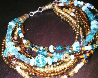 Multi-colored glass and plastic beaded anklett.